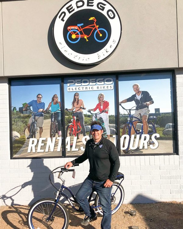 Man standing with bike outside Pedego store.